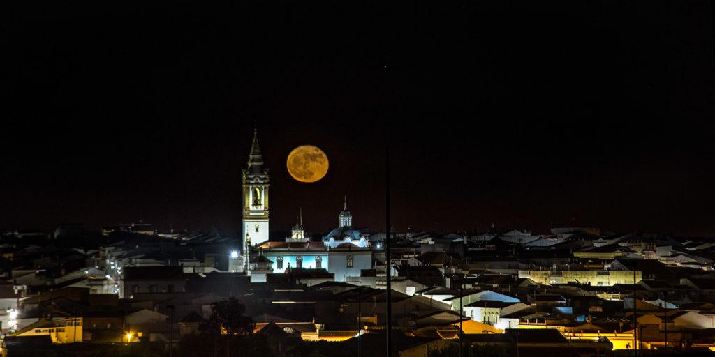 Teleobjetivo en fotografía de paisajes: Luna incluyendo iglesia, casas y pueblo